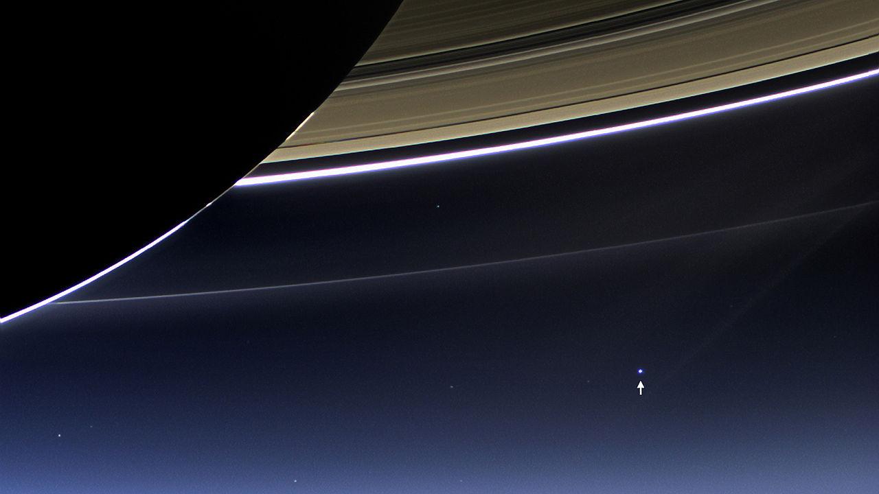 Großaufnahme von Saturn und eines Teils seiner Ringe. Im Hintergrund ist am schwarzen Himmel ein leuchtender Punkt mit einem weißen Pfeil markiert.